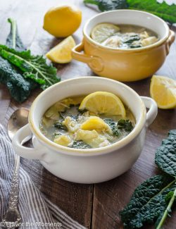 Artichoke chicken soup in white bowl with lemon and kale