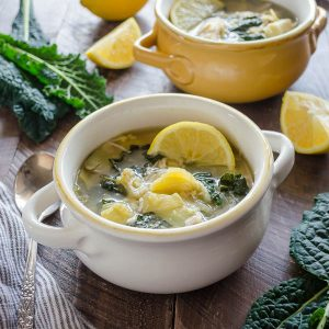 slow cooker chicken soup in white bowl with lemon slice on top