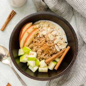 apple quinoa breakfast bowl with apples, almonds and yogurt on top