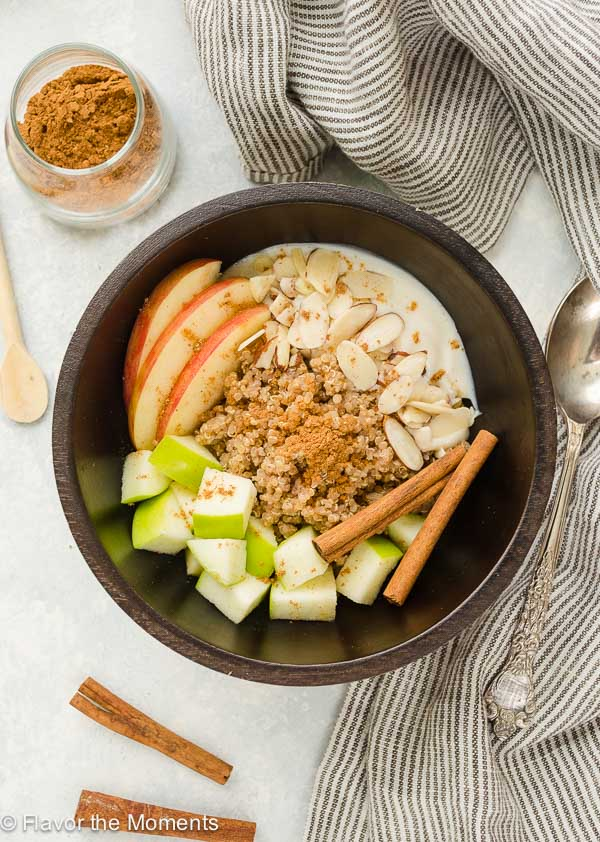 quinoa breakfast bowl with apples, chai spice and cinnamon sticks on top
