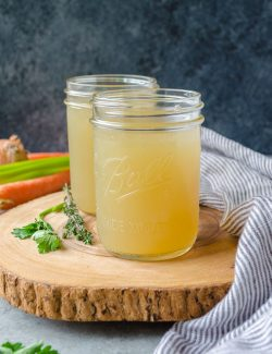 slow cooker chicken stock in jars on a wooden server