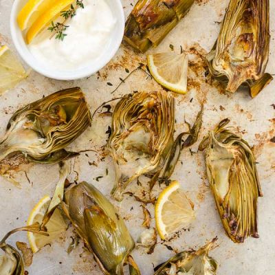 Easy Lemon Thyme Roasted Artichokes are tender oven roasted artichokes with simple instructions on how to prep artichokes. Serve with light lemon garlic parmesan Greek yogurt dip for the perfect spring appetizer!