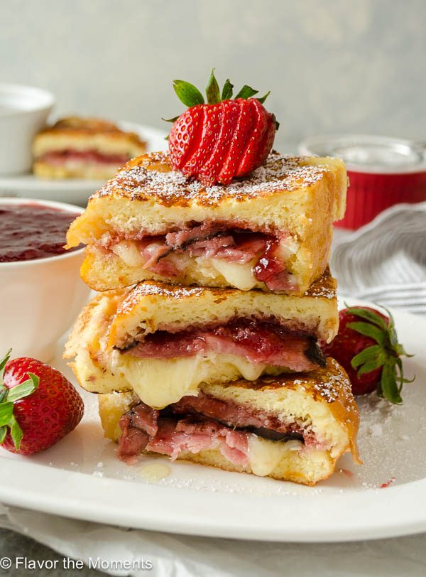 Monte cristo french toast stacked on a plate with strawberry on top