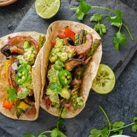 Vegetarian fajitas on platter with lime and cilantro