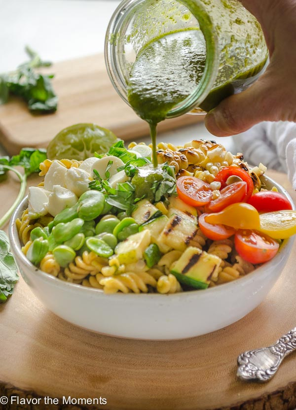 Summer succotash pasta salad in white bowl with dressing pouring over