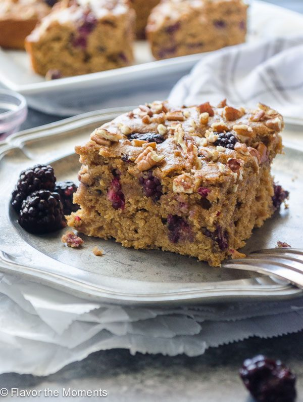 close up of blackberry snack cake on plate with blackberries