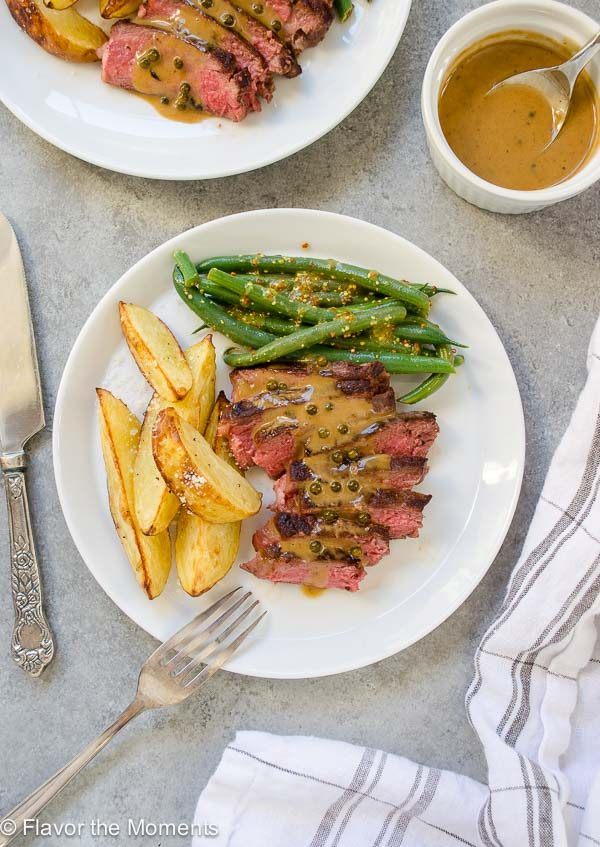 Seared steaks sliced on a plate with peppercorn sauce