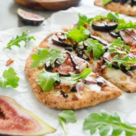 Grilled Fig, Bacon, and Arugula Flatbread Pizza is whole grain naan topped with mozzarella, fresh figs, salty bacon, and fresh arugula. It's an easy appetizer or meal that's on the table in 15 minutes! @FlavortheMoment