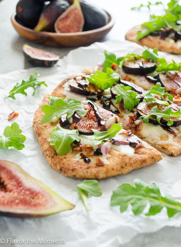Fig pizza sliced with arugula and balsamic glaze on top