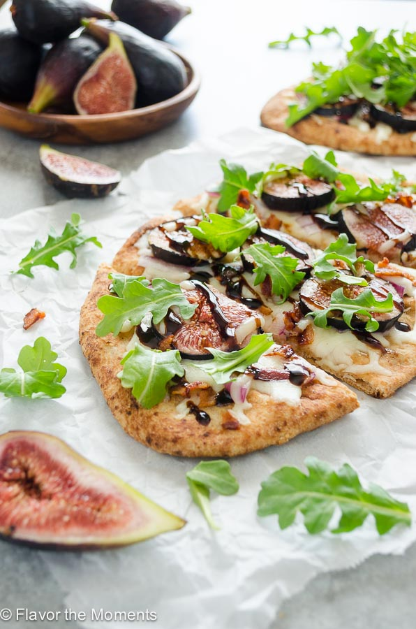 Fig arugula pizza sliced on parchment