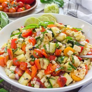 Zucchini and corn salad in white bowl with basil and lime on top