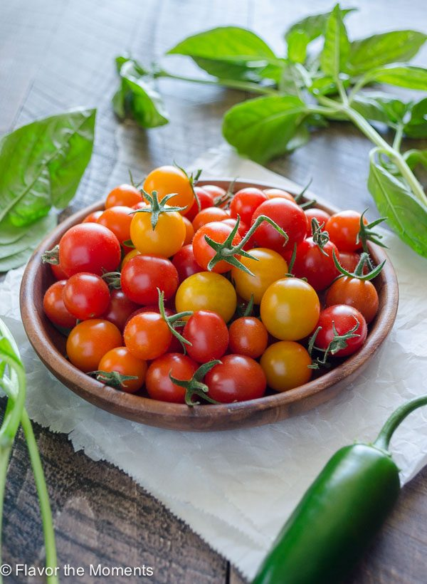 Cherry tomatoes on a plate surrounded by basil