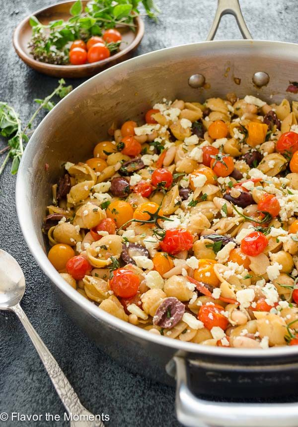 Close up of Greek pasta with burst cherry tomatoes in a skillet
