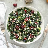 Summer kale salad in white bowl with cherries, blueberries and goat cheese