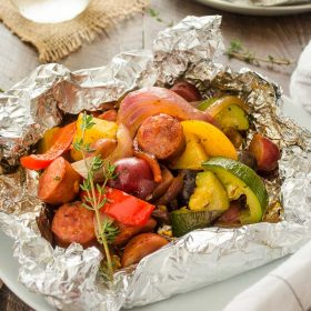 foil packet with sausage, potatoes and vegetables on a plate