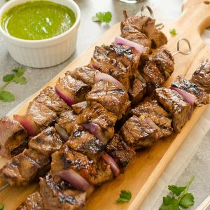 Honey soy steak kebabs on cutting board with cilantro lime sauce