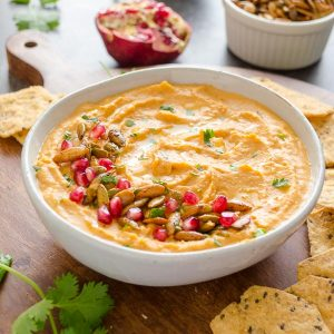 Butternut squash hummus in bowl with pomegranate and pepitas on top