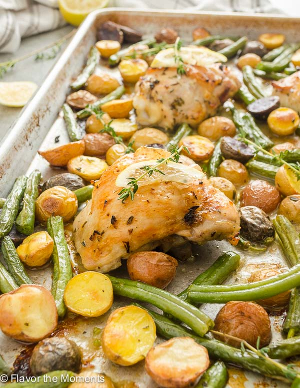sheet pan chicken thighs with lemon and thyme on top
