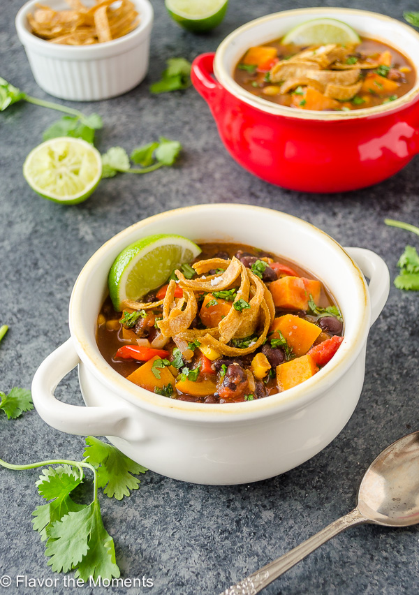 Sweet potato black bean soup in a bowl with tortilla strips and lime
