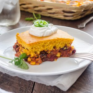 Vegetarian tamale pie on plate with sour cream and jalapeno