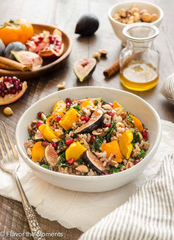Roasted Delicata Squash, Fig and Persimmon Wild Rice Salad in a bowl with fork