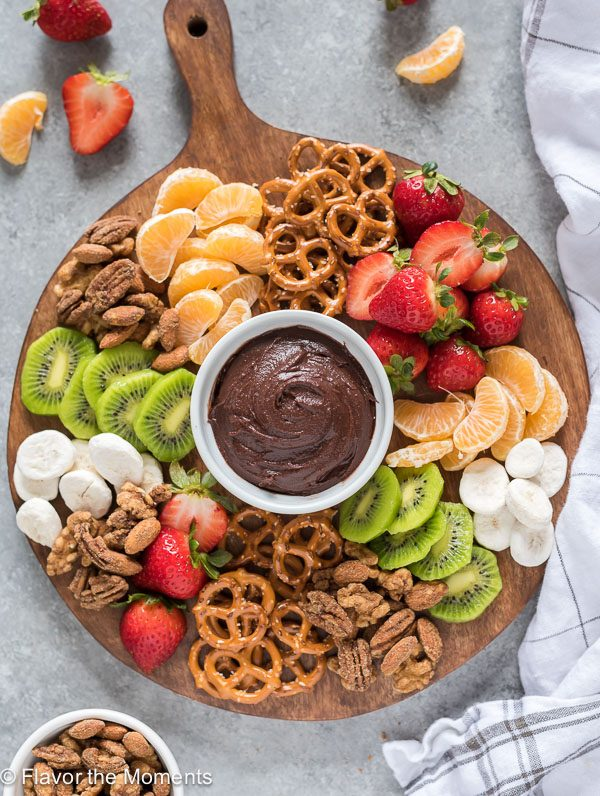 Snack board with candied nuts, chocolate hummus, fruit and pretzels