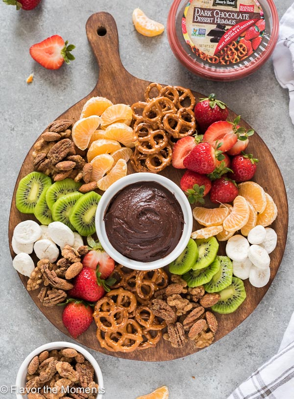 Snack board with chocolate hummus, fruit and pretzels