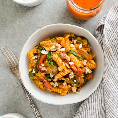 Roasted red pepper pasta in white bowl with fork and linen