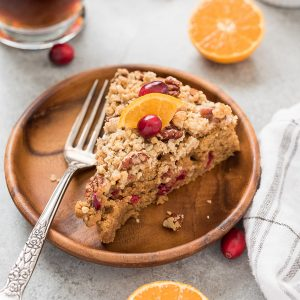 Cranberry coffee cake on a plate with cranberry and orange on top