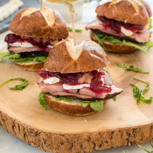Ham sliders on a serving plate with brie and cranberry sauce