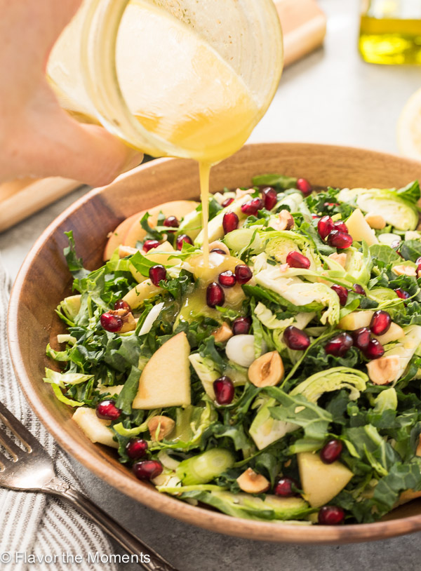 lemon vinaigrette pouring over kale brussels sprout salad