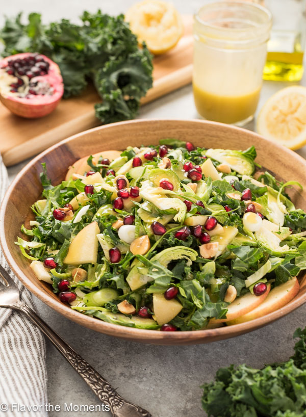 kale and brussels sprout salad with in bowl with pomegranate on top