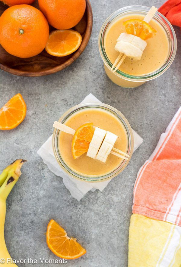 Orange cream smoothie in a jar with orange and banana skewered on a toothpick