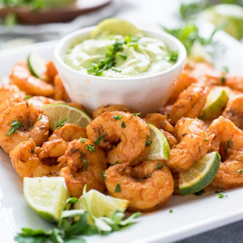 Blackened shrimp on white plate with dip, lime and parsley