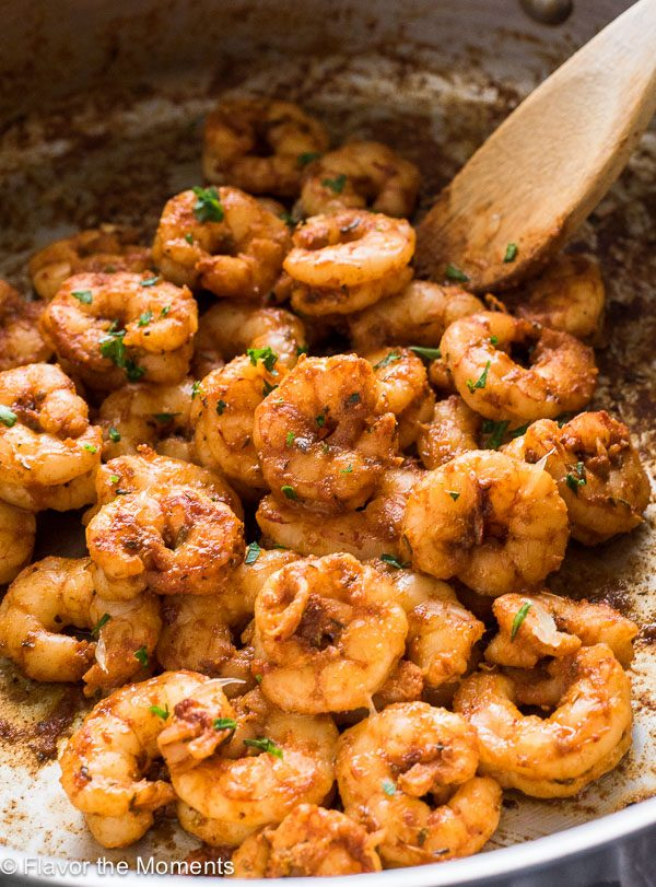 blackened shrimp in skillet with wooden spoon