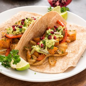 Roasted butternut squash fajitas in tortillas on a plate