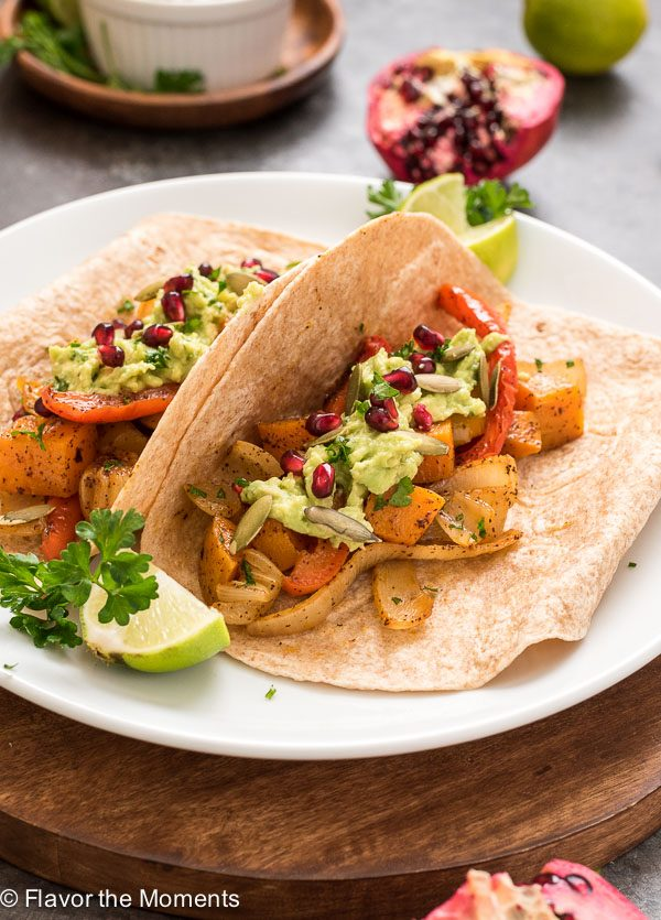 Butternut squash fajitas on a plate with pomegranate guacamole
