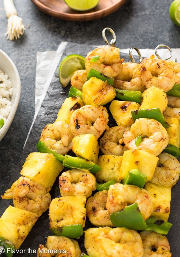 Curried shrimp skewers on platter with coconut rice