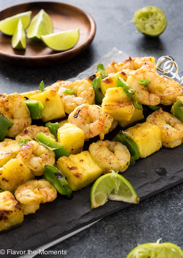 Curried shrimp skewers on platter with lime