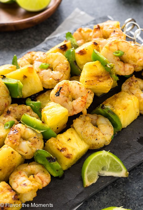 Close up of curried shrimp skewers on platter