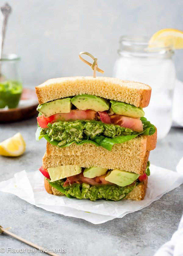 pesto chicken salad sandwich stacked on parchment paper