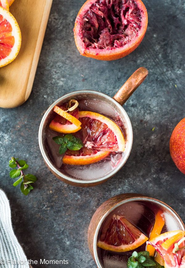 Blood orange mule in copper mug with blood oranges and mint