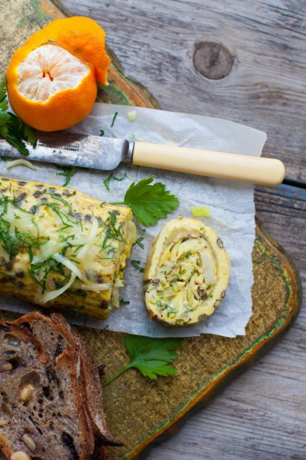 cheesy leek and lentil rolled omelet with artichokes on parchment