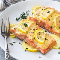 Baked lemon dijon salmon on white plate with lemon and thyme on top