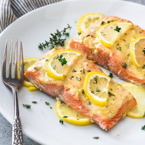 Baked lemon dijon salmon on white plate with lemon and thyme on top