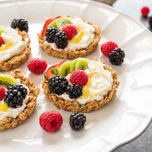 Breakfast fruit tarts on white platter with fruit and lemon curd