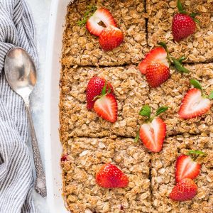 Strawberry rhubarb baked oatmeal crisp in baking dish cut into squares