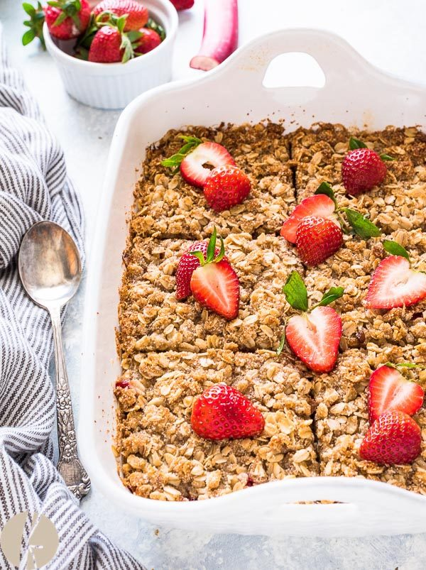 Strawberry rhubarb baked oatmeal in baking dish with strawberries on top