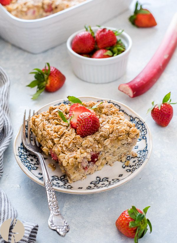 Serving of Strawberry rhubarb crisp baked oatmeal on plate with strawberry on top