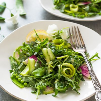 Spring Arugula Salad with Shaved Asparagus, Radish and Peas is a vibrant vegan salad tossed in a homemade lemon vinaigrette!